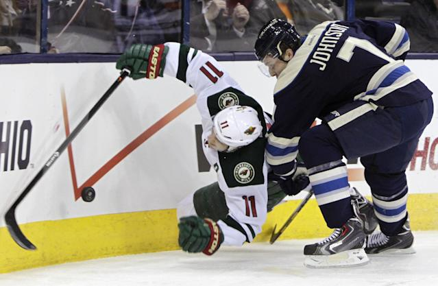 Columbus Blue Jackets' Jack Johnson, right, checks Minnesota Wild's Zach Parise during the first period of an NHL hockey game on Friday, Dec. 6, 2013, in Columbus, Ohio. (AP Photo/Jay LaPrete)