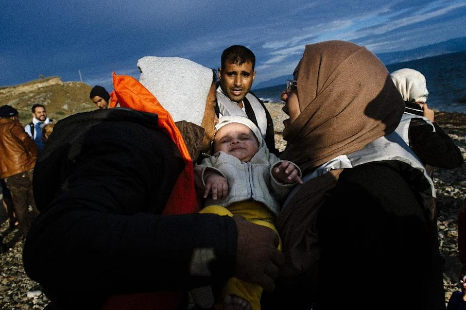 A man kisses his baby on a beach shortly after they arrived with other migrants by boat on the Greek island of Lesbos after crossing the Aegean sea from Turkey on October 10, 2015 (AFP Photo/Dimitar Dilkoff)