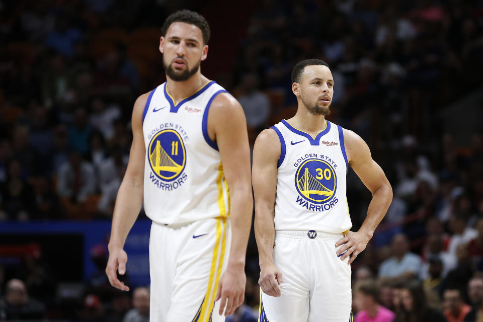 Klay Thompson #11 and Stephen Curry #30 of the Golden State Warriors look on against the Miami Heat at American Airlines Arena on February 27, 2019