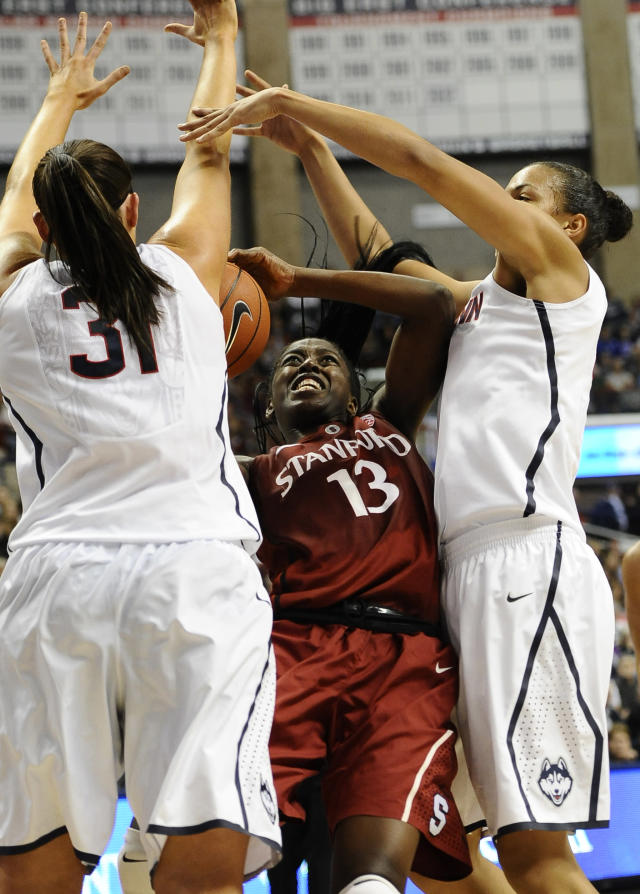 Connecticut's Stefanie Dolson, left, and Kiah Stokes, right, stop Stanford's Chiney Ogwumike, center, during the first half of an NCAA college basketball game, Monday, Nov. 11, 2013, in Storrs, Conn. (AP Photo/Jessica Hill)