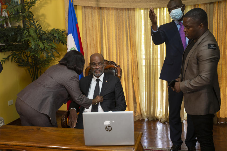 Haiti's Prime Minister Ariel Henry, center, prepares for an interview with the Associated Press at his private residence in Port-au-Prince, Tuesday, Sept. 28, 2021. (AP Photo/Joseph Odelyn)
