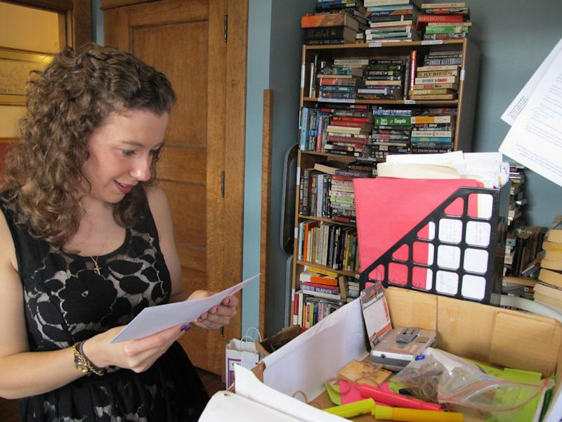 Outreach coordinator Dominique Bruno looks at unopened request letters sent to the Appalachian Prison Book Project in Morgantown, W.Va., on Nov. 13, 2012. The volunteer program has so far shipped more than 11,000 free, used books to prisoners in West Virginia, Virginia, Kentucky, Maryland, Ohio and Tennessee. (AP Photo/Vicki Smith)