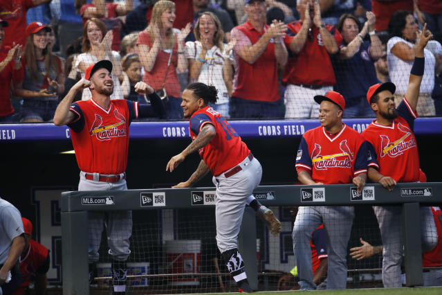 St. Louis Cardinals players celebrate in the dugout after teammate Miles Mikolas hit a two-run home run off Colorado Rockies starting pitcher Antonio Senzatela in the second inning of a baseball game Friday, Aug. 24, 2018, in Denver. (AP Photo/David Zalubowski)