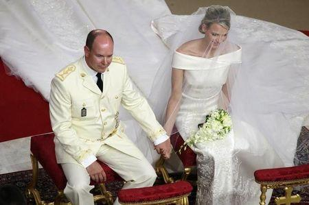 FILE PHOTO - Monaco's Prince Albert II holds hands with Princess Charlene during their religious wedding ceremony at the Palace in Monaco July 2, 2011.    REUTERS/Eric Gaillard
