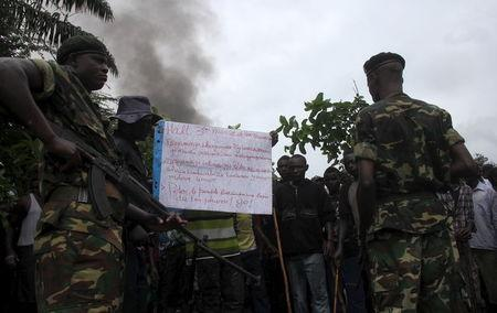 Soldiers talk to protesters as they barricade a road to demonstrate against plans by Burundian President Pierre Nkurunziza to run for a third five-year term in office, in Bujumbura