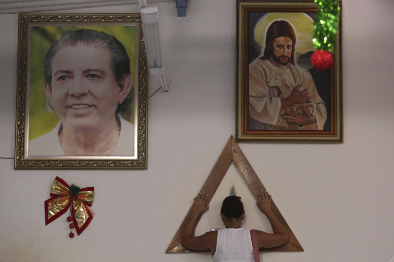 In this Jan. 4, 2019 photo, a woman places her hands in prayer on a wooden triangle, between framed images of spiritual healer Joao Teixeira de Faria and Jesus Christ, inside the Casa de Dom Inacio, in Abadiania, Brazil. Hundreds of women have accused de Faria of sexual abuse. The mounting accusations are turning the 77-year-old spiritual guru into Brazil's first major figure to go down in the #metoo era. (AP Photo/Eraldo Peres)
