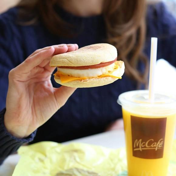 A customer holds a McDonald's breakfast sandwich.