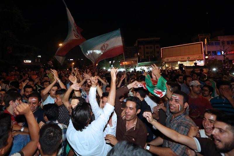 Iranian fans wave their national flag as they celebrate the World Cup on Vanak Square in Tehran, on June 21, 2014