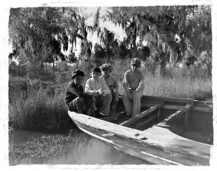 Four boys sit on a pirogue, a flat-bottomed canoe many Isle de Jean Charles residents used to get to the mainland before Island Road was built in 1953.