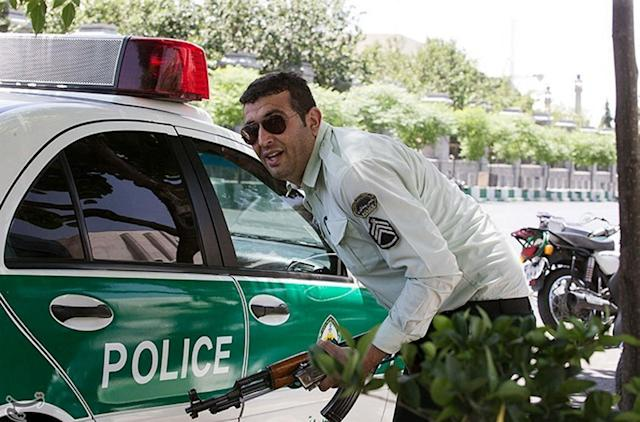 <p>An Iranian policeman takes cover during an attack on the Iranian parliament in central Tehran, Iran, June 7, 2017. (Photo: Tasnim News Agency/Handout via Reuters) </p>