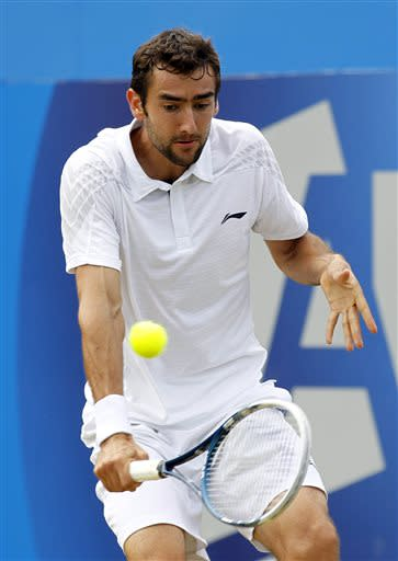 File- This June 16, 2013 file photo shows Marin Cilic of Croatia playing a return to Andy Murray of Britain during their Queen's Club grass court championships single final tennis match in London. Former top-10 player Cilic has been suspended nine months for a doping violation. The ban was back-dated to May 1, so Cilic can return to competition Jan. 31, the International Tennis Federation said Monday Sept. 16, 2013. (AP Photo/Sang Tan, File)