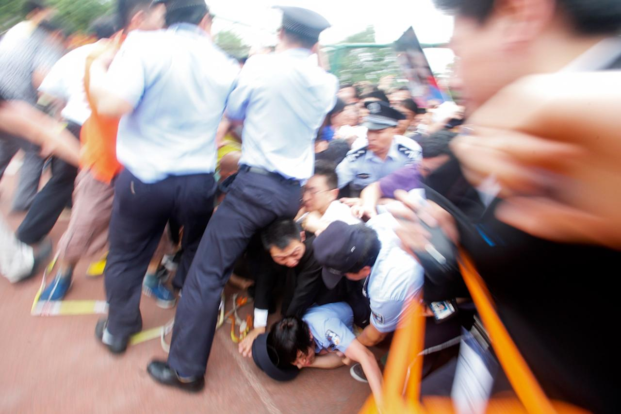 SHANGHAI, CHINA - JUNE 20: (CHINA OUT) Police officers fail to stop people from falling to the ground in a crush as they surge forward as David Beckham arrives at Tongji University on June 20, 2013 in Shanghai, China. The stampede is reported to have left five people injured and hospitalised. (Photo by Getty Images)
