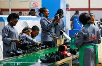 Women workers inspect shoes at a Bata shoe factory in Abuja