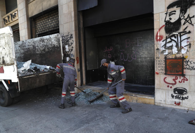 Workers remove broken glass of a window shop that was damaged by protesters during an anti-government rally in Beirut, Lebanon, Friday, June 12, 2020. Lebanon's prime minister held an emergency Cabinet meeting Friday, hours after demonstrators shut roads across the country with burning tires in renewed nationwide protests spurred by a plunging national currency and economic crisis. (AP Photo/Hussein Malla)