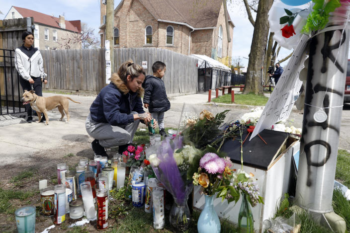 A resident lights a candle where  13-year-old Adam Toledo was shot by police in Chicago on April 16, 2021. / Credit: Shafkat Anowar / AP