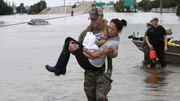 PHOTO: Houston Police SWAT officer Daryl Hudeck carries Catherine Pham and her 13-month-old son Aiden after rescuing them from their home surrounded by floodwaters from Tropical Storm Harvey, Aug. 27, 2017, in Houston.  (David J. Phillip/AP)