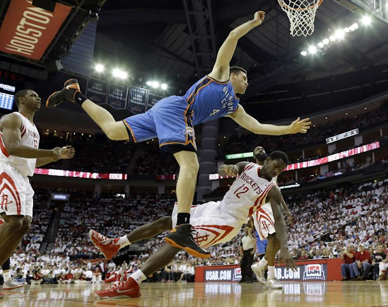 Houston Rockets' Patrick Beverley (12) falls backward while blocking Oklahoma City Thunder's Nick Collison (4) during the first quarter of Game 3 in a first-round NBA basketball playoff series Saturday, April 27, 2013, in Houston. Beverley was called for a blocking foul. (AP Photo/David J. Phillip)