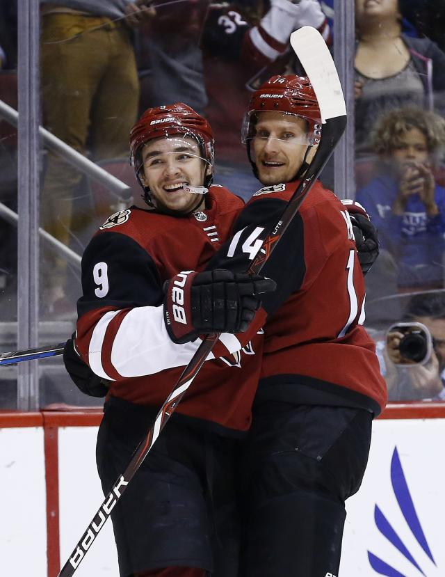 Arizona Coyotes right wing Richard Panik (14) celebrates his goal against the Calgary Flames with center Clayton Keller (9) during the second period of an NHL hockey game Monday, March 19, 2018, in Glendale, Ariz. (AP Photo/Ross D. Franklin)