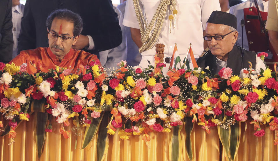 Maharashtra state Governor Bhagat Singh Koshyari, right, watches Shiv Sena party leader Uddhav Thackeray sign a document during a swearing-in-ceremony in Mumbai, Thursday, Nov. 28, 2019. Supporters of the Shiv Sena, Nationalist Congress Party (NCP) and the Congress party thronged Shivaji Park to watch their leaders take oath of office. (AP Photo/Rafiq Maqbool)