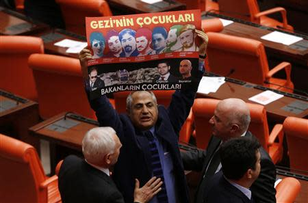 Cam holds a banner during a debate at the parliament on draft budget in Ankara
