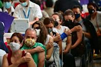 People wait after receiving doses of the Pfizer-BioNTech shot at a vaccination center set up in Mexico City's Vasconcelos Library on May 11, 2021