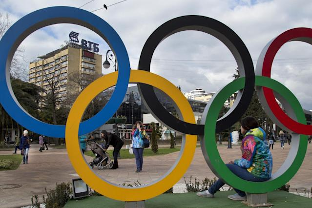 A Russian Olympic volunteer poses for snapshots next to the Olympic rings in Sochi, Russia, Tuesday, Feb. 4, 2014. The opening ceremony for the 2014 Winter Olympics will be held on Feb. 7. (AP Photo/Bernat Armangue)
