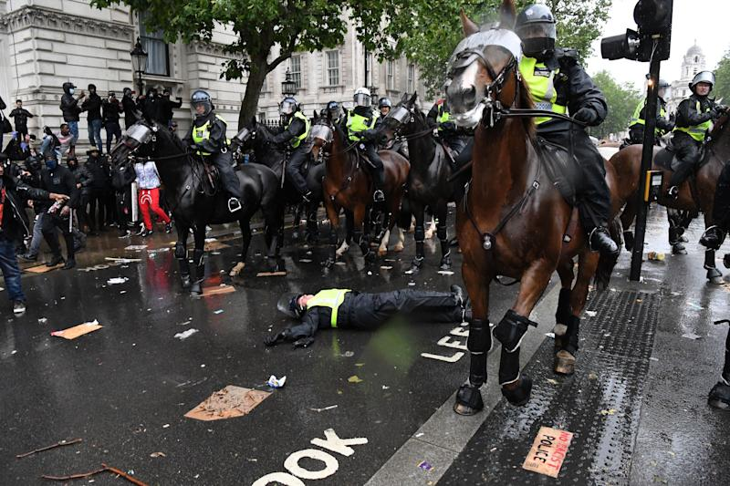 A mounted police officer lays on the road after being unseated from their horse, during a demonstration on Whitehall. (Photo: DANIEL LEAL-OLIVAS via Getty Images)