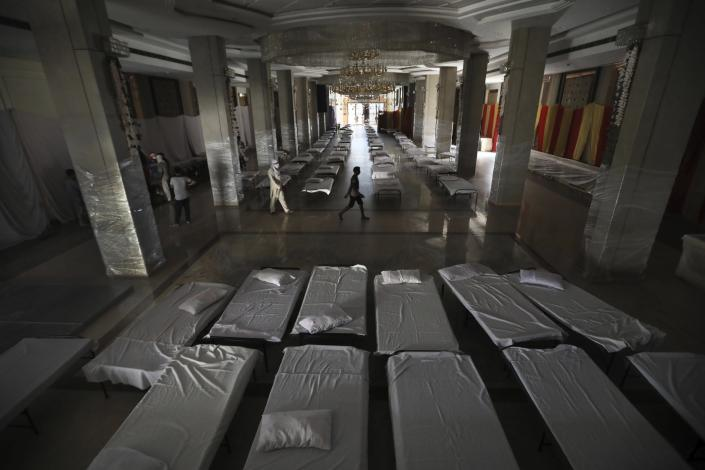 FILE - In this Monday, June 15, 2020 file photo workers walk across a banquet hall which is generally used for weddings that has been converted to makeshift coronavirus hospital as the Indian capital struggles to contain a spike in cases. in New Delhi, India. (AP Photo/Manish Swarup, File)