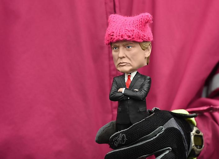 <p>A protester, holding a Donald Trump doll wearing a pink cap, marches in Washington, DC, during the Womens March on January 21, 2017. (ROBYN BECK/AFP/Getty Images) </p>