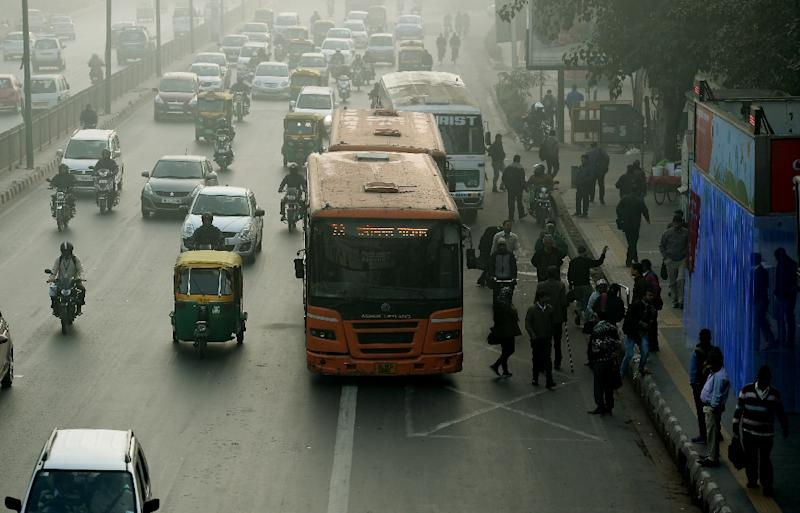Indian commuters wait for their ride at a bus stop