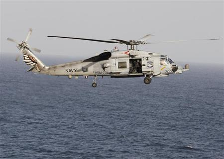 A Sikorsky SH-60 Seahawk helicopter flies near the Nimitz-class aircraft carrier USS Abraham Lincoln (CVN 72) during a transit through the Strait of Hormuz