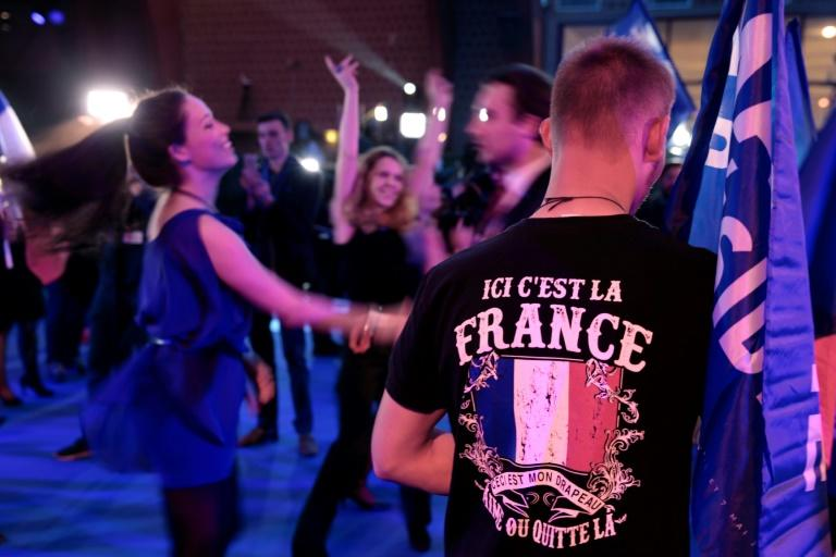 National Front supporters dance after projections that party leader Marine Le Pen will contest the runoff in France's presidential election on May 7