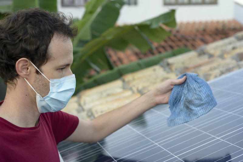 Man holding dirty rag while cleaning solar panel for inspection
