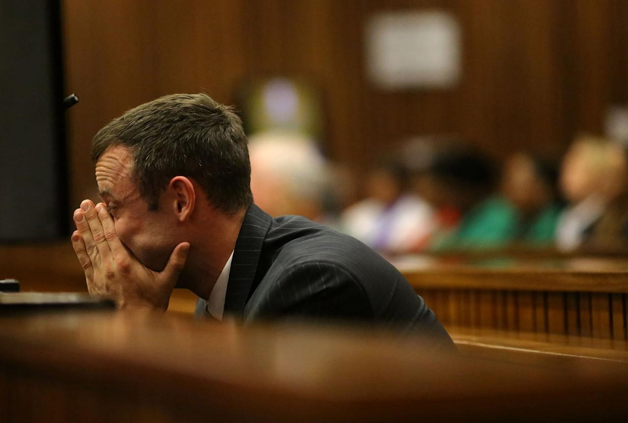 Oscar Pistorius sits in the dock as he listens to cross questioning about the events surrounding the shooting death of his girlfriend Reeva Steenkamp, in court during his trial in Pretoria, South Africa, Monday, March 10, 2014. Pistorius is charged with the shooting death of his girlfriend Steenkamp in 2013. (AP Photo/Siphiwe Sibeko, Pool)