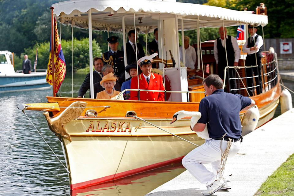 Queen Elizabeth II, accompanied by Swan Marker David Barber (red jacket), watches from the steam launch 'Alaska' during the 2009 ceremony. (Getty Images)