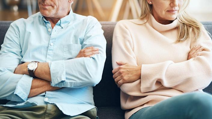 mature couple sitting on the sofa with their arms folded after an argument.
