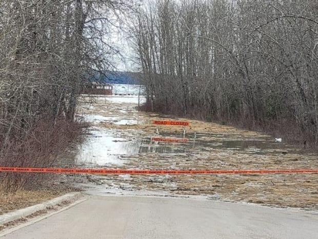A road closed sign and caution tape blocking a flooded road in Fort Simpson. Tim Tomezynski, Tulita's Fire Chief described the floods as horrific: 'Since my time here, this has been the worst that I have heard of.'