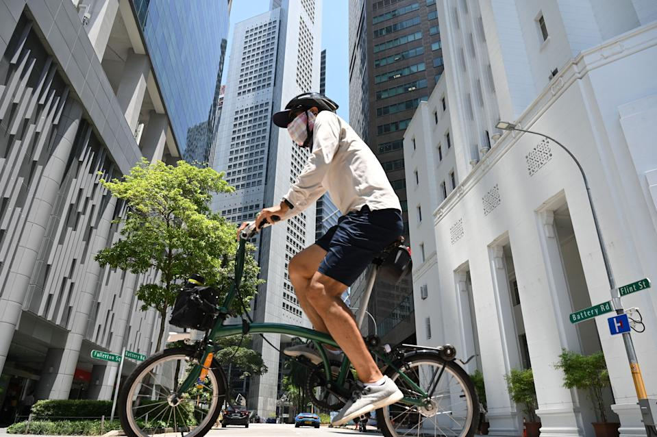 A man seen riding a bicycle at Raffles Place on 20 April. (PHOTO: Getty Images)