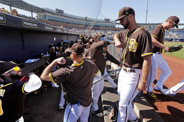 PHOTO: San Diego Padres players bump elbows rather than slap hands while heading into the dugout between innings of a spring training baseball game against the Kansas City Royals, March 4, 2020, in Peoria, Ariz. (Elaine Thompson/AP)