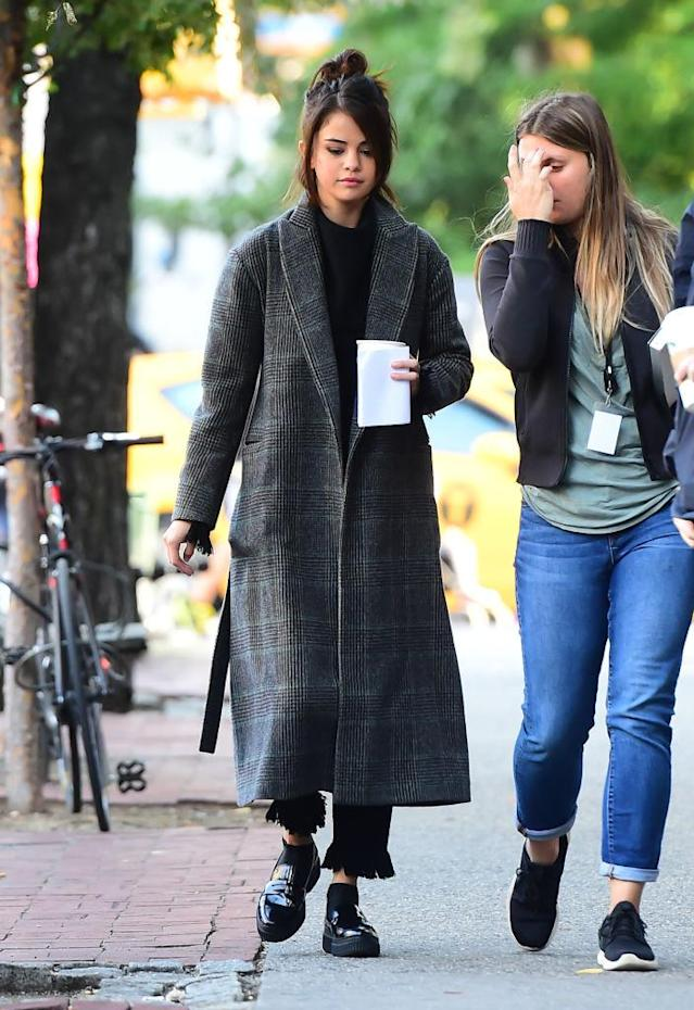 <p>Monday was a day of filming, where Gomez was spotted twice shooting for an untitled Woody Allen film. For her morning call time, she was wearing her long coat again with an all-black outfit underneath. (Photo: Getty Images) </p>