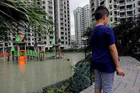 A child stands next to a flooded playground after Typhoon Hato hits Hong Kong, China August 23, 2017. REUTERS/Tyrone Siu