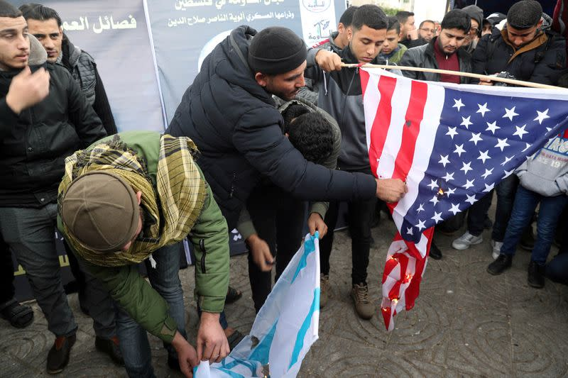 Palestinians burn representations of a U.S. flag and an Israeli flag during a protest against the killing of Iranian Major-General Qassem Soleimani, in Gaza