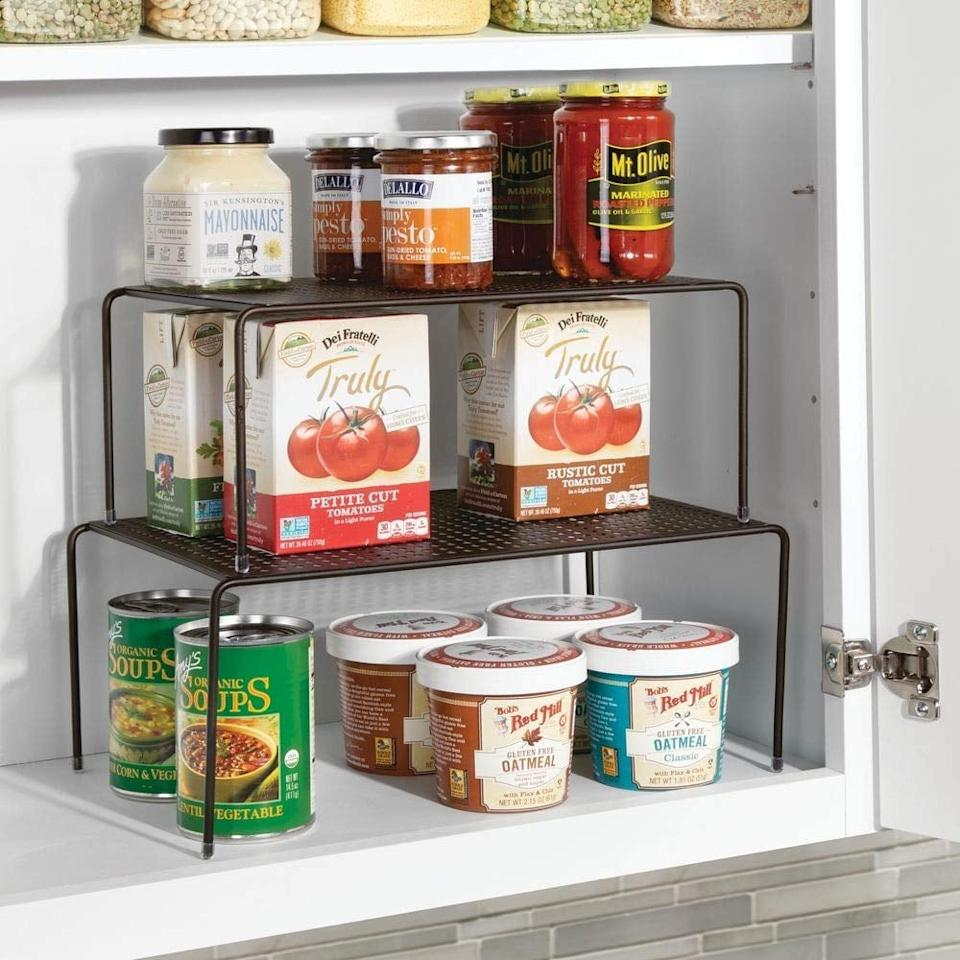 """<p>Make your shelves feel triple the size with this <a href=""""https://www.popsugar.com/buy/mDesign-Adjustable-Metal-Kitchen-Cabinet-492988?p_name=mDesign%20Adjustable%20Metal%20Kitchen%20Cabinet&retailer=amazon.com&pid=492988&price=20&evar1=casa%3Aus&evar9=47137466&evar98=https%3A%2F%2Fwww.popsugar.com%2Fhome%2Fphoto-gallery%2F47137466%2Fimage%2F47137475%2FmDesign-Adjustable-Metal-Kitchen-Cabinet&list1=organization%2Ckitchens%2Csmall%20space%20living%2Chome%20organization%2Chome%20shopping&prop13=mobile&pdata=1"""" rel=""""nofollow"""" data-shoppable-link=""""1"""" target=""""_blank"""" class=""""ga-track"""" data-ga-category=""""Related"""" data-ga-label=""""https://www.amazon.com/mDesign-Adjustable-Kitchen-Countertop-Organizer/dp/B07BVNPC92/ref=sr_1_53?crid=2XPKXWACED22E&amp;keywords=mdesign+under+%2425&amp;qid=1569003962&amp;s=gateway&amp;sprefix=mde&amp;sr=8-53"""" data-ga-action=""""In-Line Links"""">mDesign Adjustable Metal Kitchen Cabinet</a> ($20).</p>"""