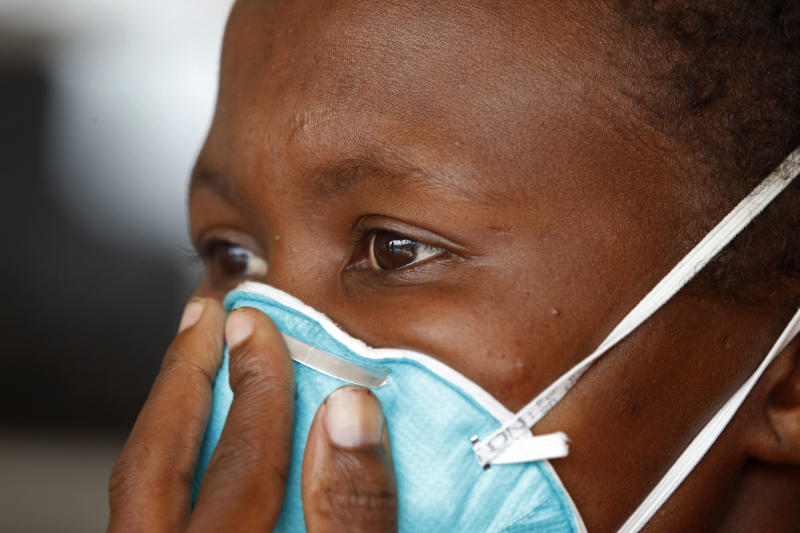 FILE - A woman suffering from tuberculosis covers her face at a clinic in the township of Khayelitsha, South Africa, in this file photo dated Thursday, March 24, 2011. It is announced Monday Feb. 4, 2013, that the world's most advanced tuberculosis vaccine failed to protect babies against the airborne infectious disease, according to a new study that tested the shot in South Africa.(AP Photo/Schalk van Zuydam, FILE )