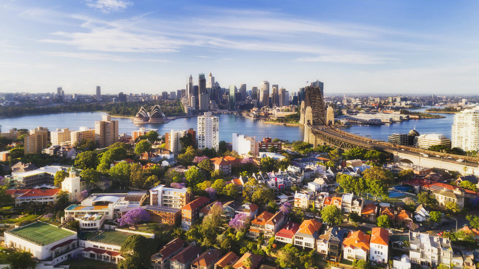 Sydney Harbour lower north Shore against city CBD waterfront around Circular quay and the Sydney Harbour bridge over red roofs of low-rise residential houses in aerial view. Source: Getty Images