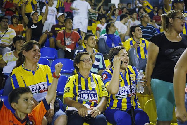 In this Oct. 18, 2014 photo, fans of the Deportivo Capiata soccer team celebrate their team's goal at a national league match against Cerro Porteno in Capiata, Paraguay. The young team has a tiny fan base, and everything about the club is modest: its dressing room, workout room and stadium amenities. (AP Photo/Jorge Saenz)