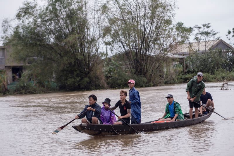 Local residents row a boat to a pickup point for delivering aid packages to residents affected by heavy flood in Quang An Commune
