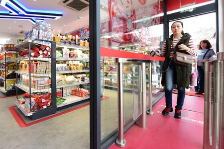 Woman enters a JD.com's unmanned store with facial recognition technology, by scanning QR code with her phone on a detection machine at the store entrance in Xian, Shaanxi