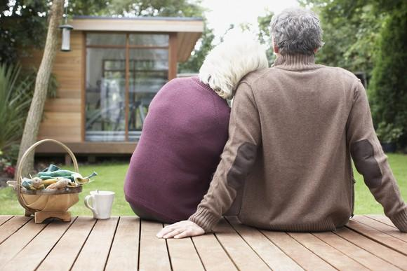 Older man and woman sitting on a deck. Woman rests her head on the man's shoulder.