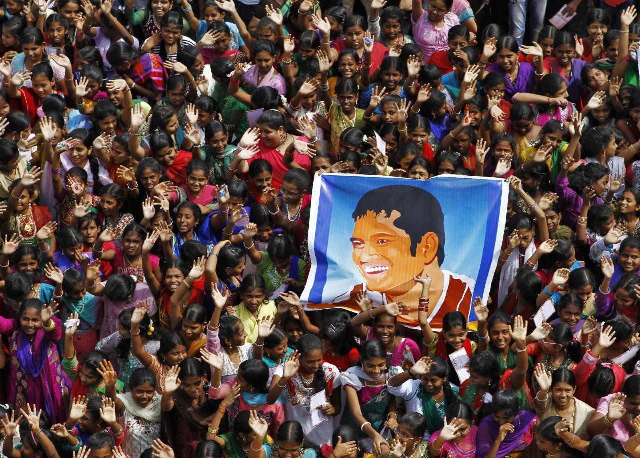 School children wave as they hold a poster of Indian cricketer Sachin Tendulkar at an event to honour him inside a school in the southern Indian city of Chennai November 14, 2013. Cricket-crazy India will have a lump in the throat as its favourite son, Tendulkar, walks out for one last time this week to play the game he has dominated for nearly a quarter of a century. The 'Little Master' will bring the curtain down on a glittering 24-year career at the age of 40 when he plays his 200th test match, against West Indies, at his home ground starting on Thursday. REUTERS/Babu (INDIA - Tags: SPORT CRICKET)